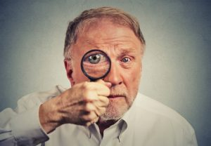 Closeup surprised man looking through a magnifying glass