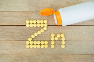 Yellow pills forming shape to Zn alphabet on wood background zinc