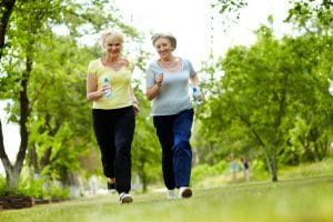 Portrait of two senior females running outdoors