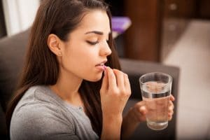 Cute young brunette taking a pill with a glass of water at home