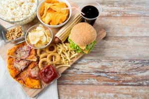 fast food, junk-food and unhealthy eating concept - close up of fast food snacks and coca cola drink on wooden table