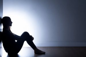 Teenager with depression sitting alone in dark room