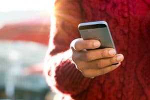 Close up of a young woman's hand typing text message on her smartphone. African young woman is typing on touch screen mobile phone. Close up of female hand texting a message phone outdoor.