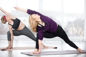 Fitness, stretching practice, group of two attractive happy smiling fit mature women working out in sports club, doing Extended Side Angle posture, utthita parshvakonasana pose in class, full length