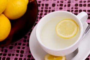 A white china tea-cup of hot water and a slice of lemon, next to a bowl of lemons