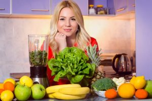 Gorgeous young blonde next to a juicer, fruits and vegetables (smoothie ingredients), healthy lifestyle, healthy food concept