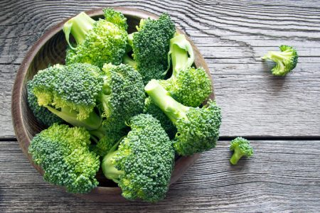 Raw broccoli in a bowl on rustic background