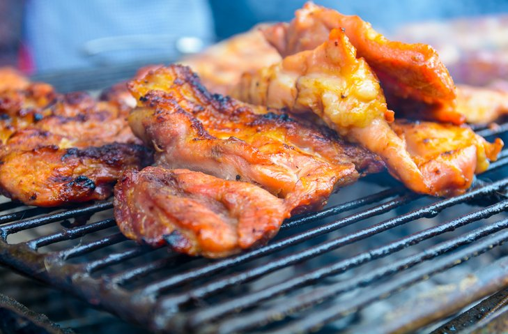 close up of grilled pork on the grill at market in Thailand.