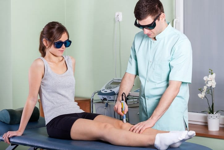 Doctor treating a patient with laser physiotherapy
