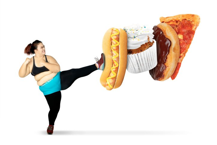Diet concept. Young obese woman refuses to eat junk foods by kicking a hot dog, cupcake, donut, and pizza. Isolated on white background