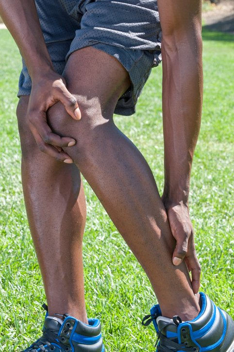 Closeup of lean muscular African American male runner massaging injured leg suffering from Achilles tendonitis as he stands in shorts on green lawn