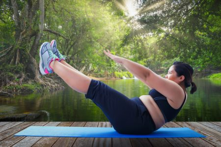 asian fat woman take v shape six pack course in the morning on wooden platform outdoor