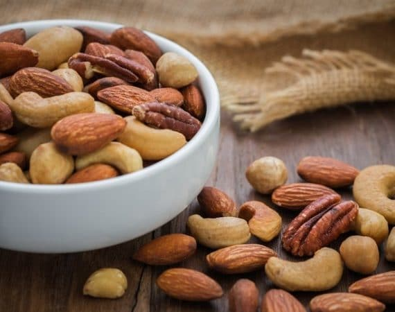 Mixed nuts on wooden table and bowl