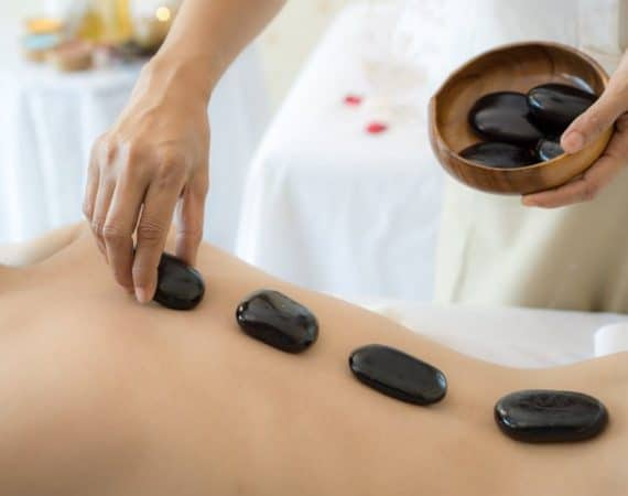 close up beautiful and healthy woman during a back stone therapy massage in spa salon