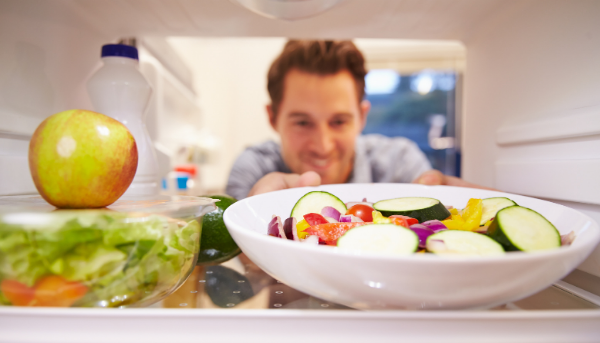 Man reaching for salad in fridge